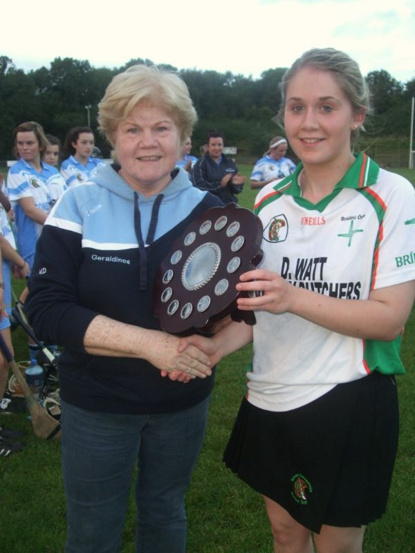 County Committee member Marie Doherty presents the Junior Camogie shield to team Captain Caoimhe McAleenan