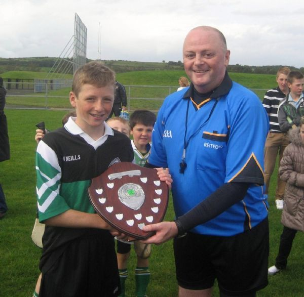 John McHenry presents St Brendan's captain, Niall, with the U12 Shield.