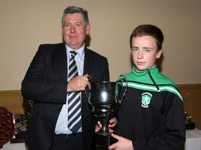Sean McKay receives the U14 Football Championship trophy from Colum Walsh